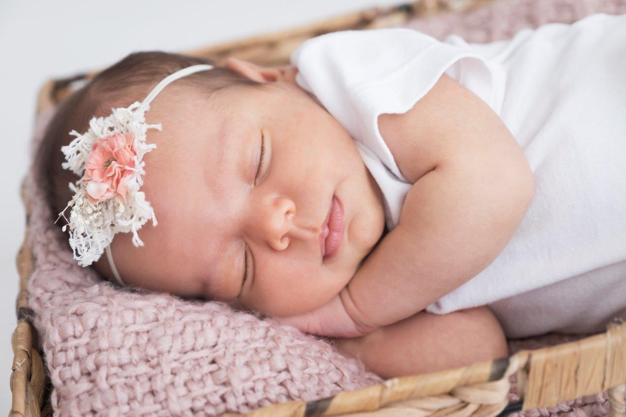 baby sleeping in basket with pink flower on head