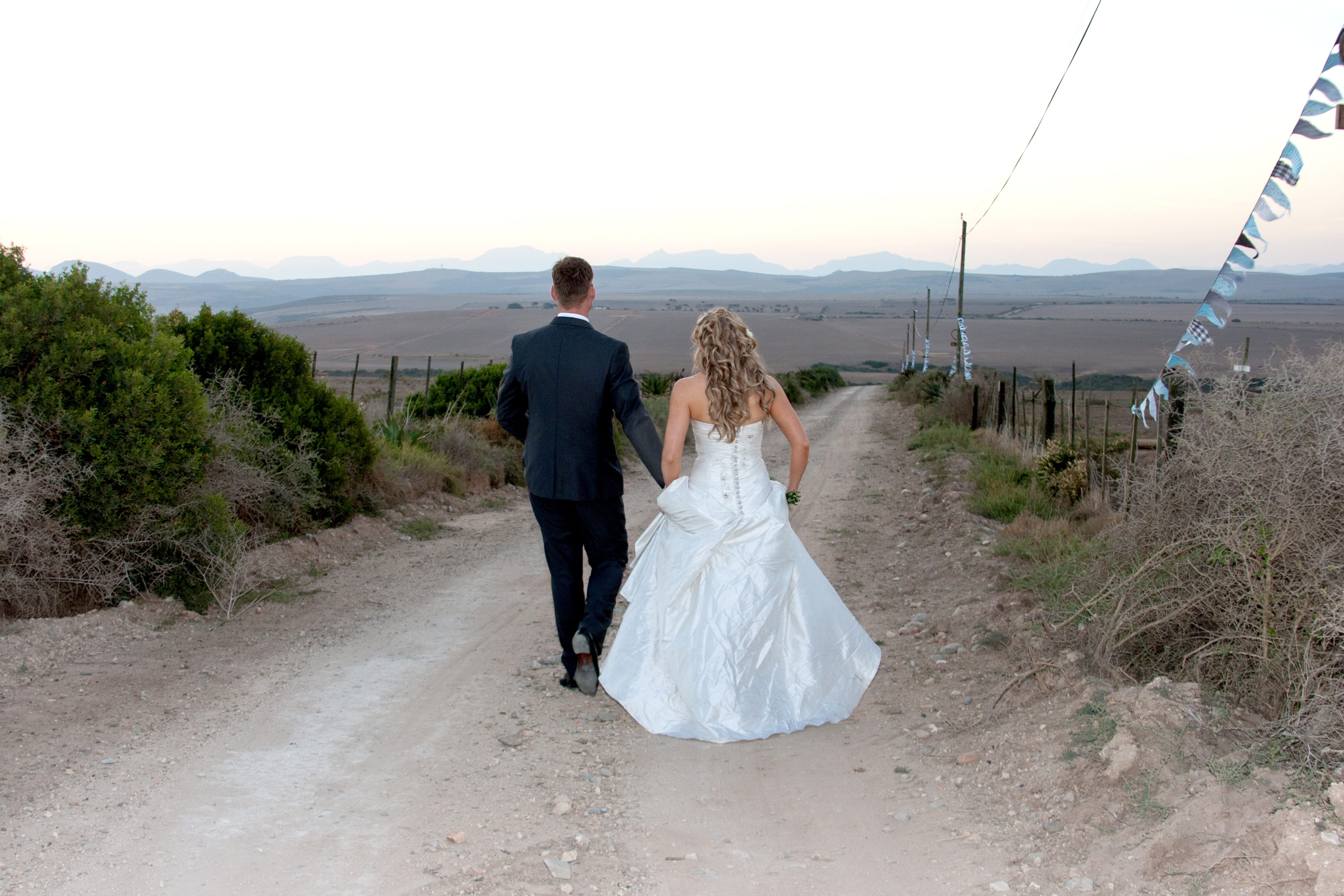 wedding couple walking down a dirt road