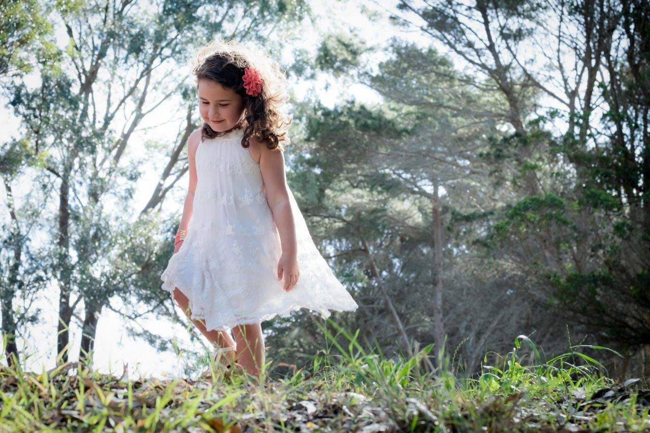 little girl in the park in a white dress