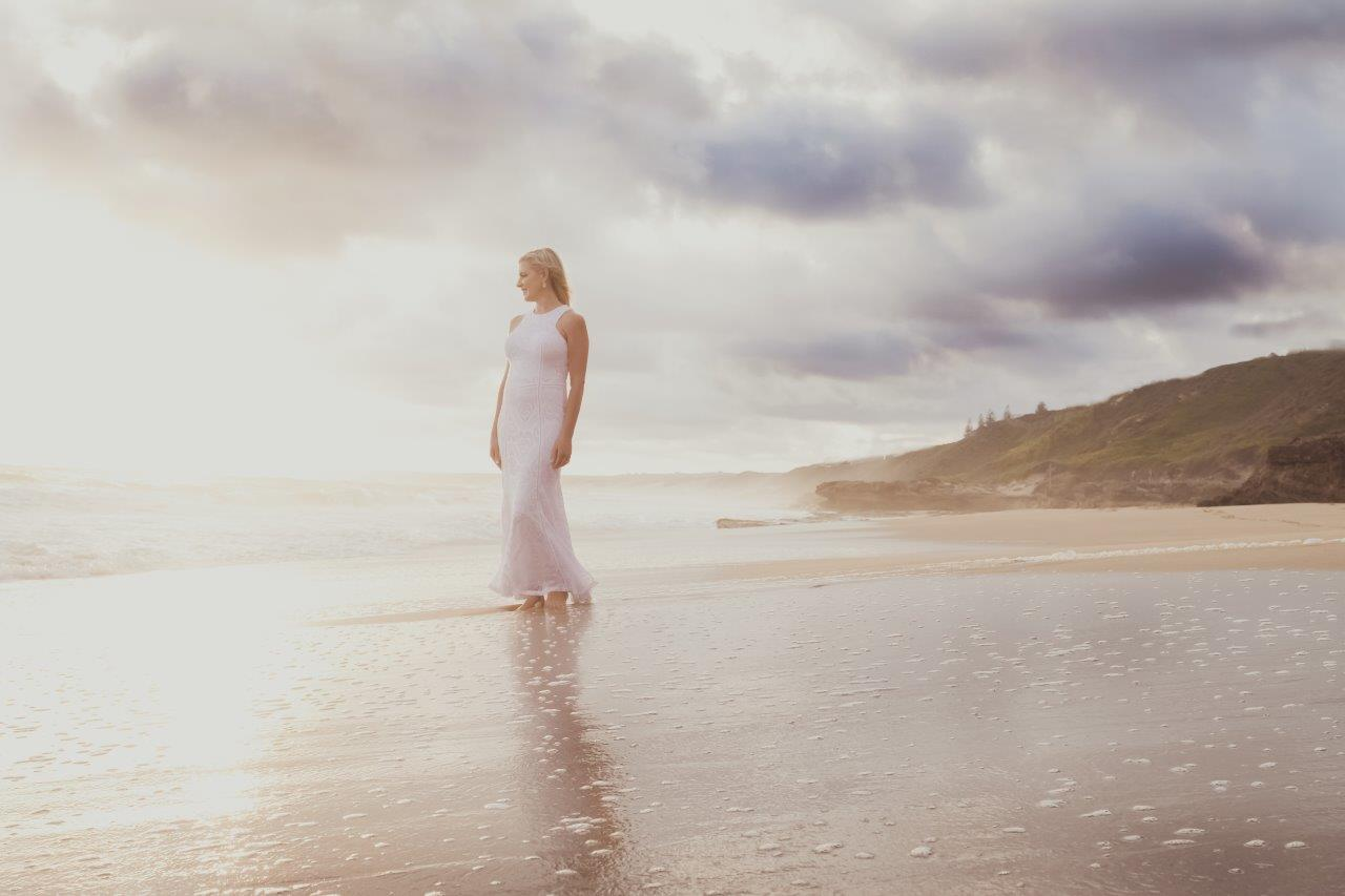 women on the beach in a white dress