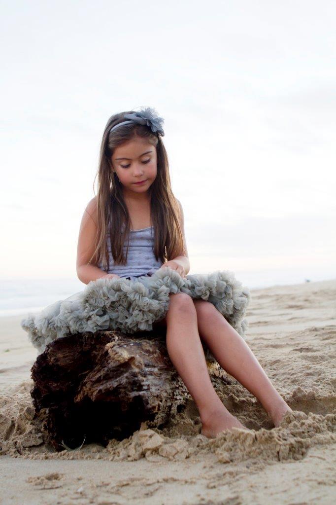 girl sitting on log on the beach