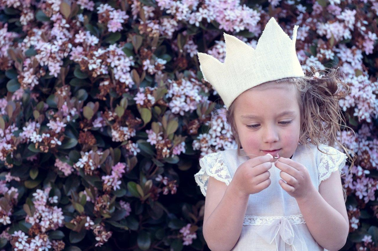 girl looking at floor with crown on her head